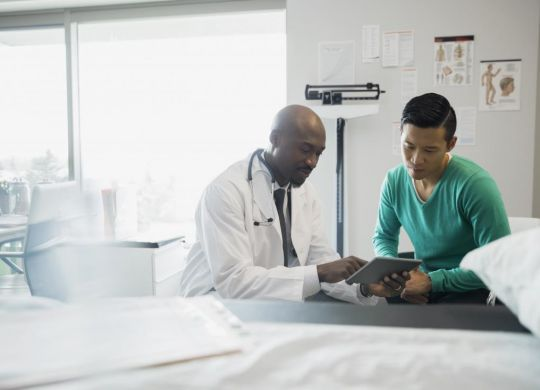 doctor-showing-patient-something-on-tablet